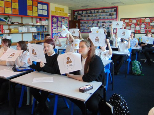 Pupils demonstrating whether they think a news article is real or fake by holding up a sign that says either 'real' or 'fake'